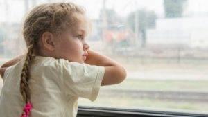 niña triste en la ventana