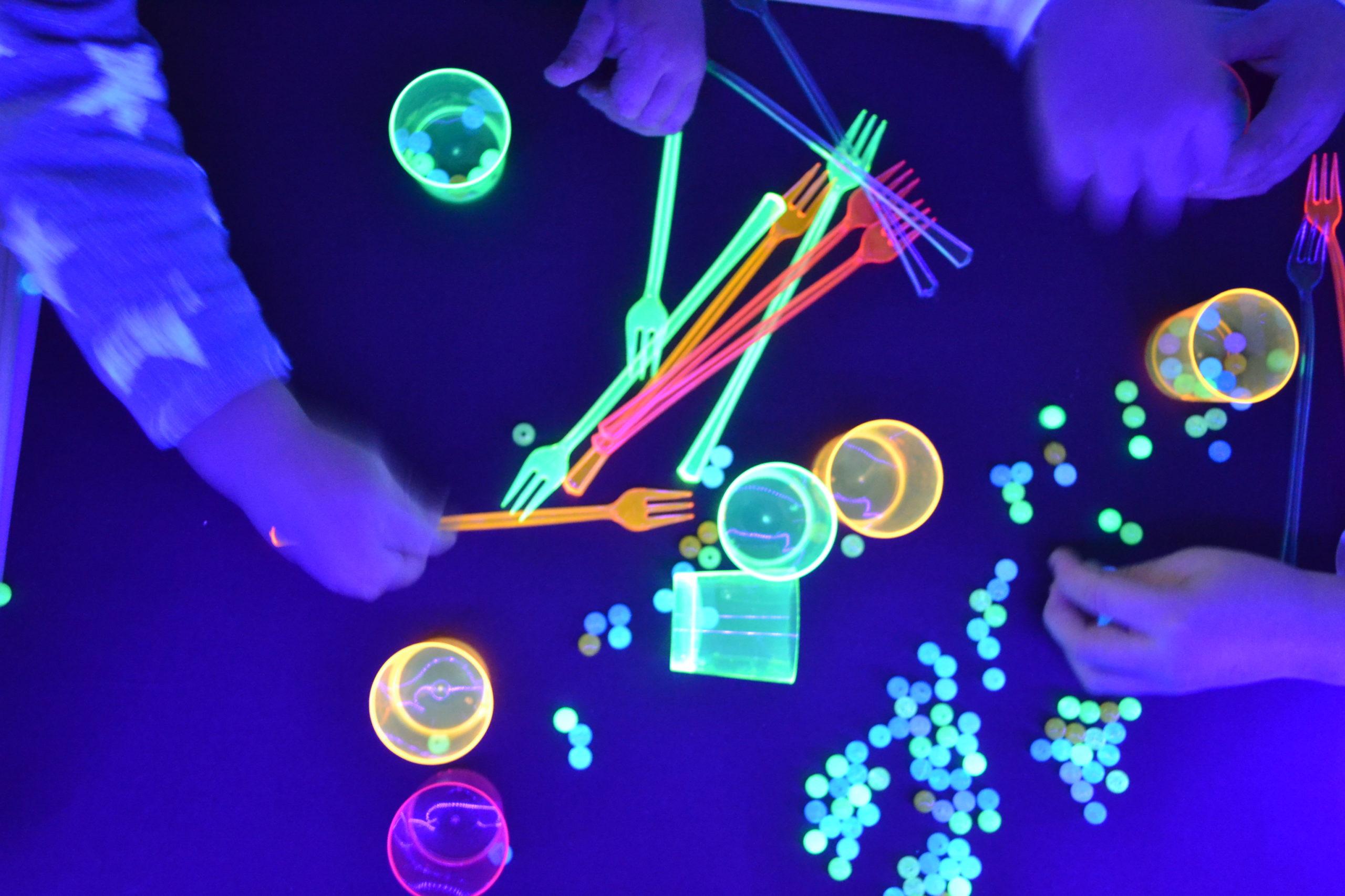 juego de luz negra con vasos y  bolas