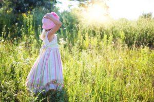 Niña en el campo sujetando su sombrero