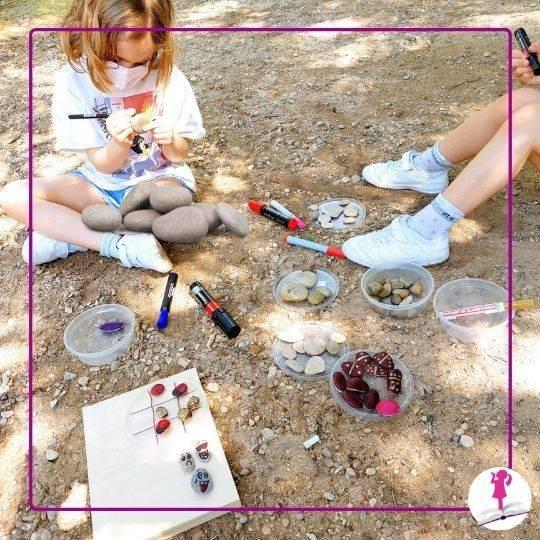 niñas pintando piedras en el río